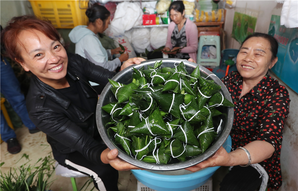 Two women display their hand-made Zongzi at the Zhuanxin market in Kunming, Yunnan province, June 1.