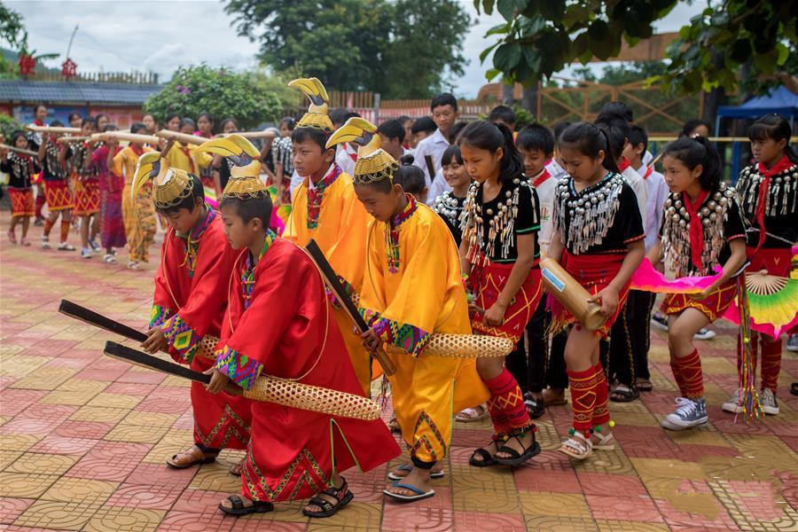 Boys dressing colorful gowns and hornbill-shaped headwear lead the dance