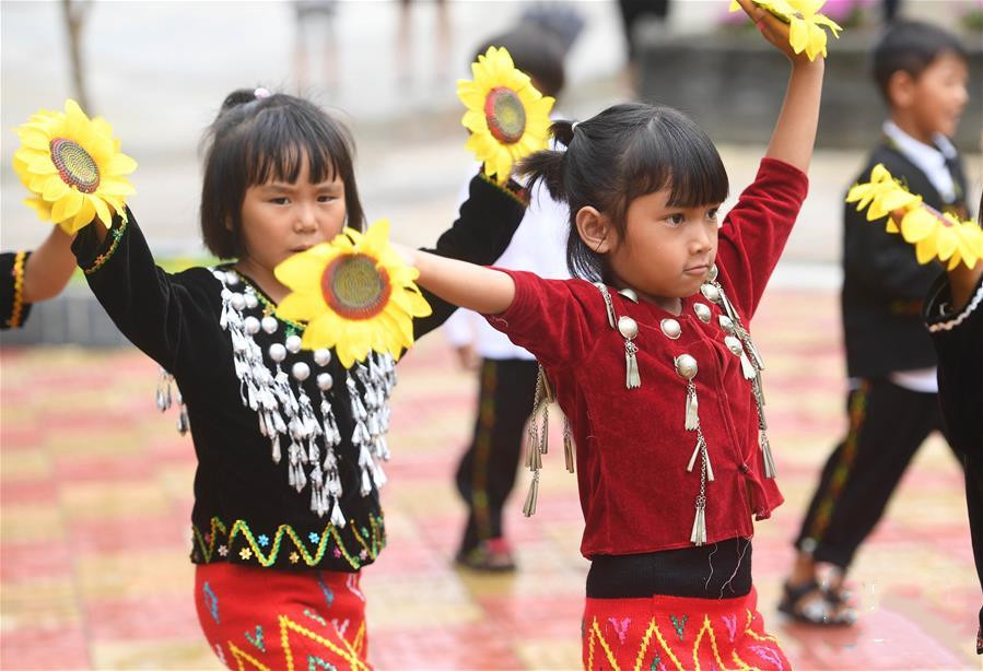 Jingpo girls dance with flowers in their hands
