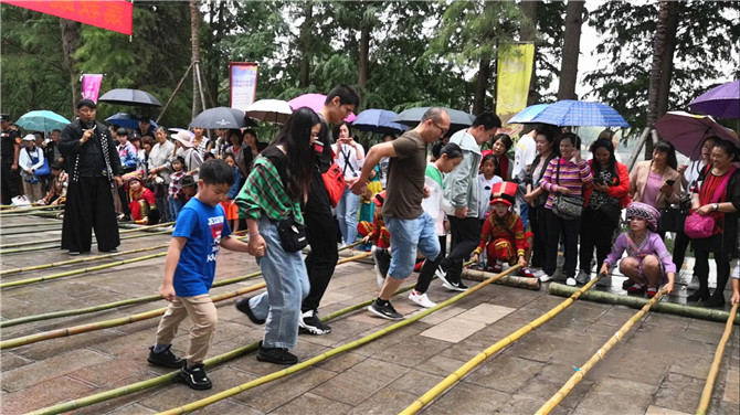 Tourists try bamboo pole dance