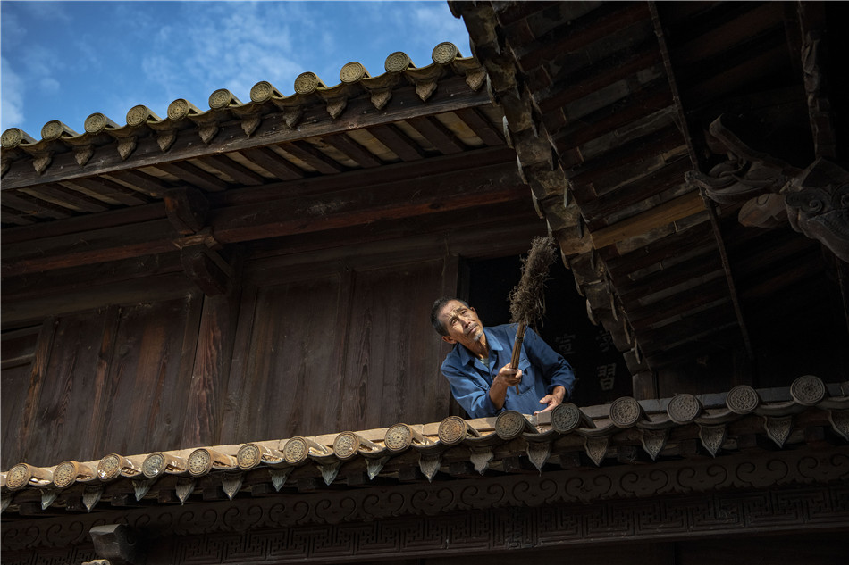 Yang Guobao, a local resident from Shiping cleans up his upturned roof with care