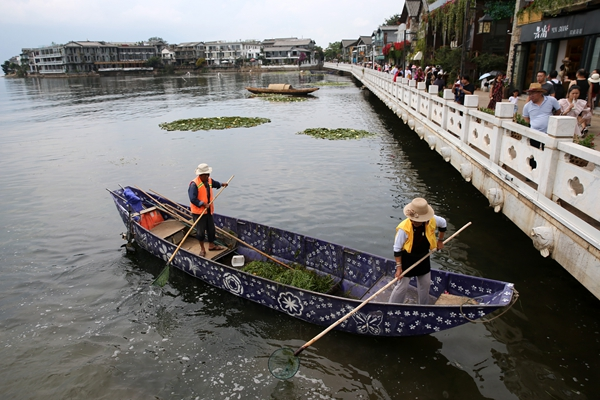 Environmental protection staff in Shuanglang town remove debris from the lake