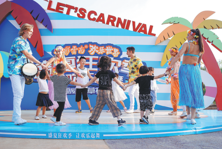 Foreign employees dance with children at Colorful Yunnan Paradise, a theme park in Kunming, Yunnan province