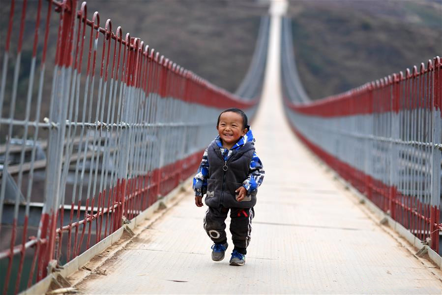 A child walks on a bridge spanning the Niulan River in southwest China on Dec. 11, 2019