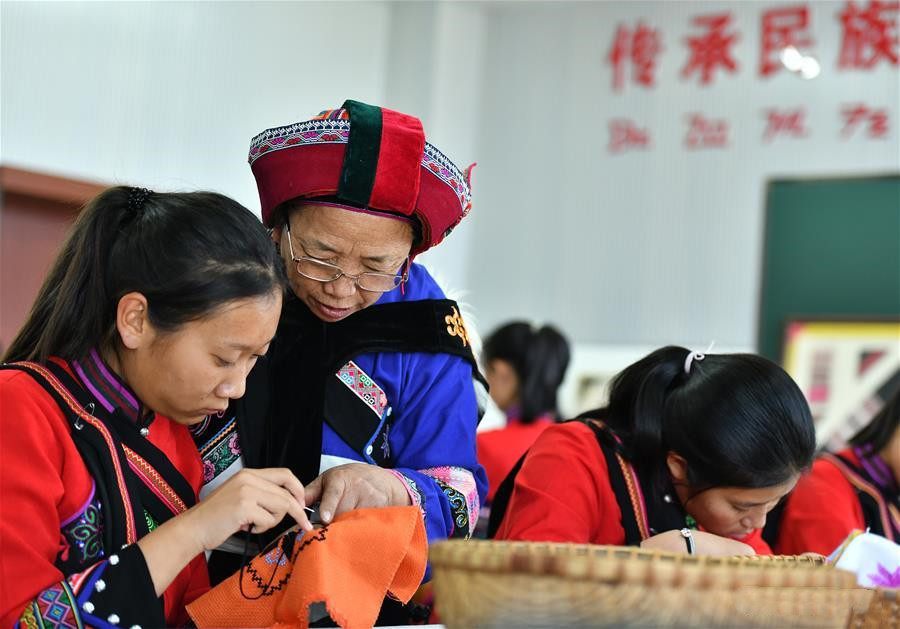 National intangible cultural heritage inheritor Bi Yueying guides a student in Shilin County of Kunming, Yunnan