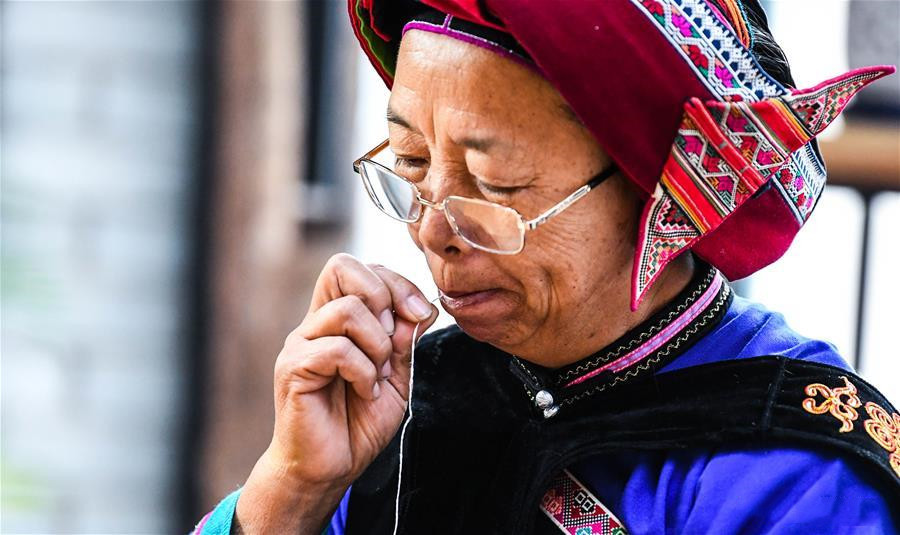 National intangible cultural heritage inheritor Bi Yueying makes embroidery at her workshop in Shilin county of Kunming, Yunnan