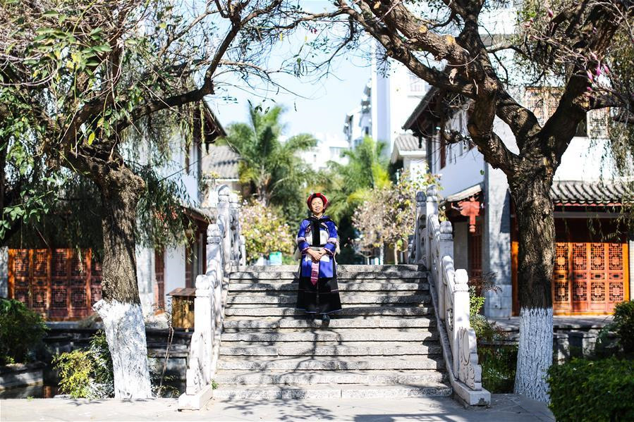 National intangible cultural heritage inheritor Bi Yueying stands on a stone bridge in Shilin County of Kunming, Yunnan