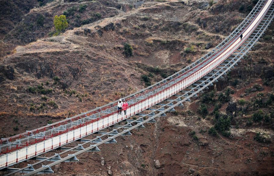 People walk on a bridge spanning the Niulan River in southwest China on Dec. 11, 2019